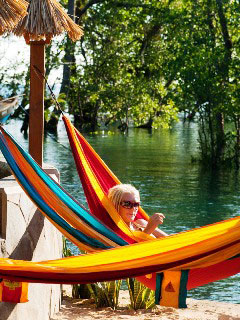 Relax in a hammock at the water's edge at Living Colours Resort