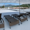 The partially shaded sundeck with sun loungers