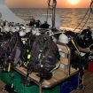 Assembled dive gear on the dive deck with underseat baskets