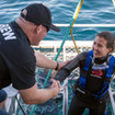 Another happy is helped onboard after a surface cage dive