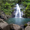 A waterfall cascades into a large pool on this Pacific island